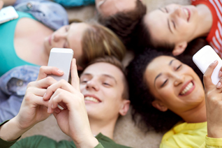 education, people and technology concept - close up of students or friends with smartphones lying on floor in circle